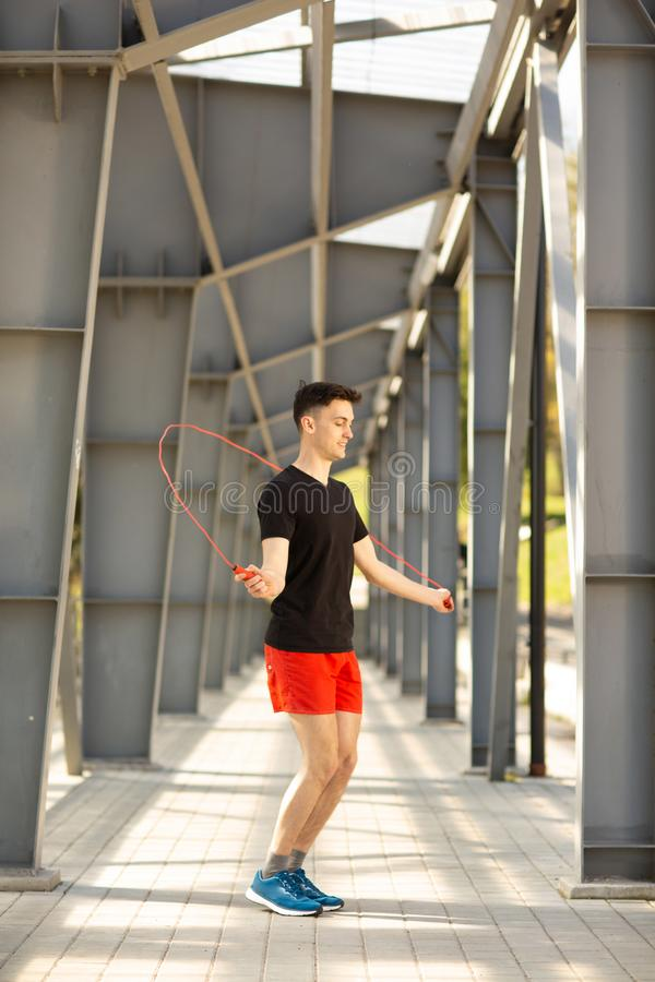 Молодой человек прыгая с веревочкой скачки outdoors Концепция работать и образа жизни стоковые изображения rf