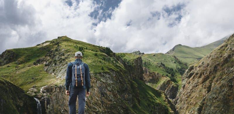 Молодой человек путешественника стоя na górze скалы в горах и наслаждаясь взглядом природы, вид сзади стоковые фото