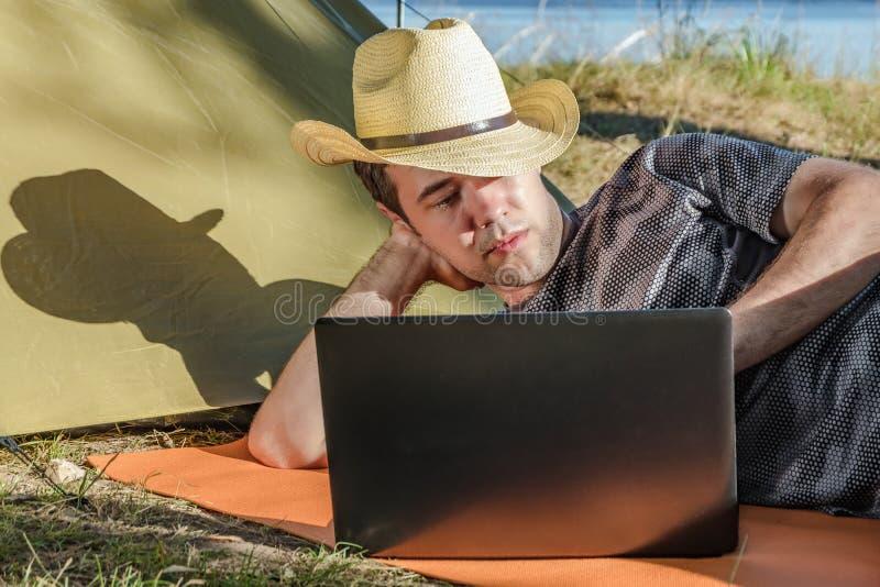 Молодой человек работая и отдыхая в природе Человек в шляпе лежит в природе около шатра с компьтер-книжкой и работой стоковое изображение rf