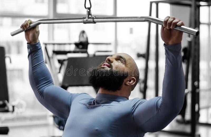 Молодой человек работая крепко в спортзале для того чтобы завоевать в спорт, тренировке pulldown стоковые изображения rf