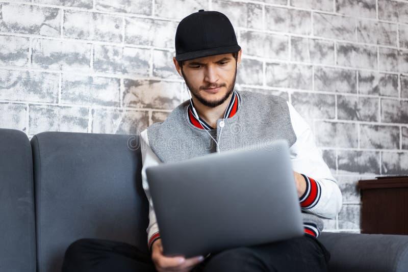 Молодой человек работая на ноутбуке на предпосылке серой кирпичной стены стоковое фото
