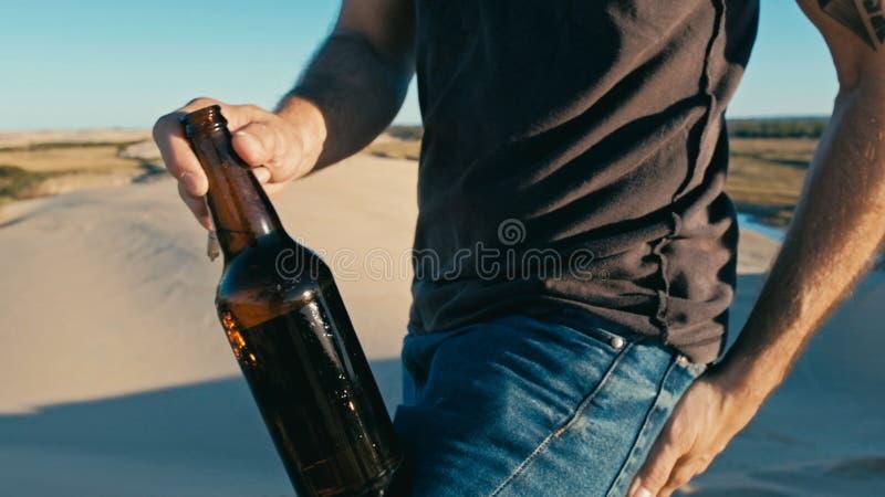 молодой человек раскрывая бутылку пива внешнюю в песчанных дюнах пустыни стоковое фото