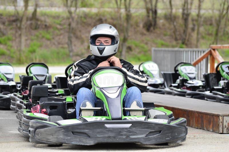 Молодой человек регулирует шлем на автомобиле Идти-Kart на гоночном треке спортивной площадки стоковое фото