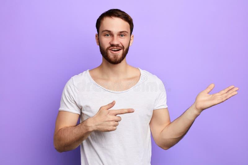 Молодой человек рекомендует товары счастливый внушительный бородатый человек указывая прочь стоковые изображения rf