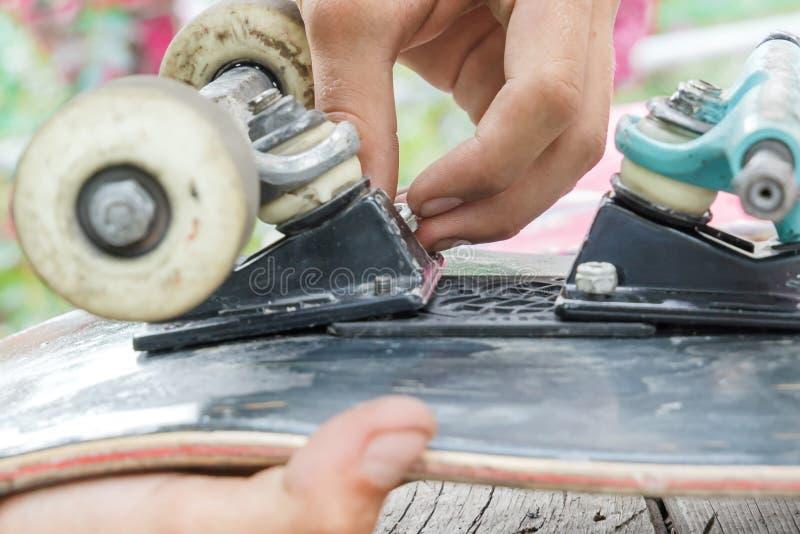 Молодой человек ремонтирует колеса на скейтборде стоковое изображение