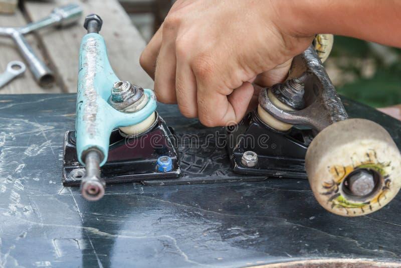Молодой человек ремонтирует колеса на скейтборде стоковые изображения rf