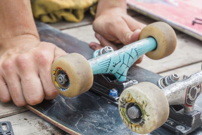 Молодой человек ремонтирует комплекты скейтборда и колеса изменений стоковая фотография rf