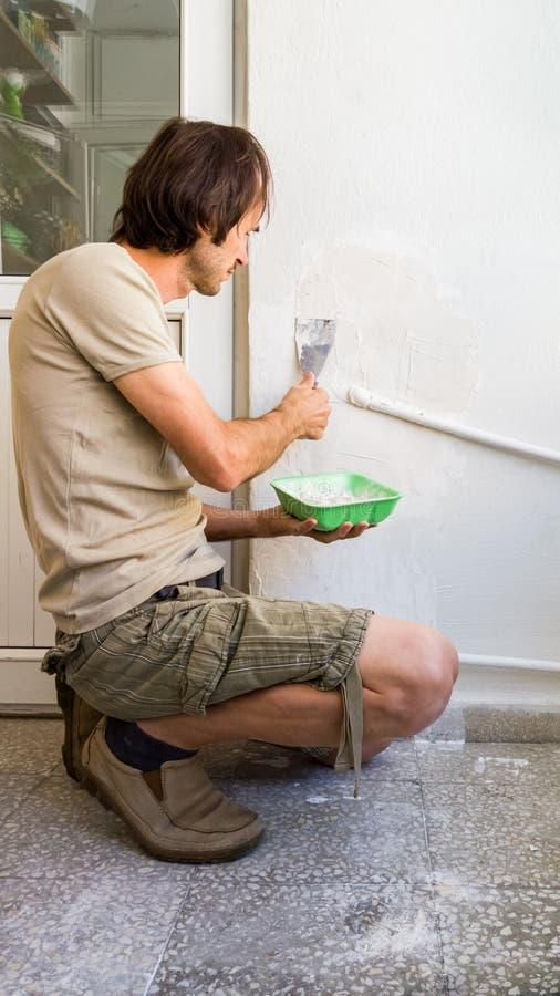 Молодой человек ремонтируя стену на его квартире, прикладывая смешивание гипсолита на стене стоковые фотографии rf
