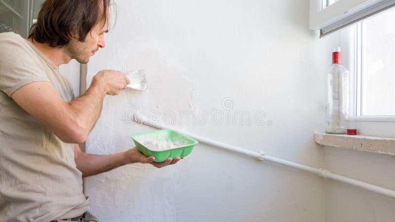Молодой человек ремонтируя стену на его квартире, прикладывая смешивание гипсолита на стене стоковые изображения rf