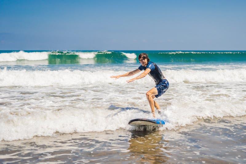 Молодой человек, серфер beginner учит заниматься серфингом на пене моря на b стоковое изображение rf