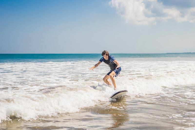 Молодой человек, серфер beginner учит заниматься серфингом на пене моря на b стоковая фотография