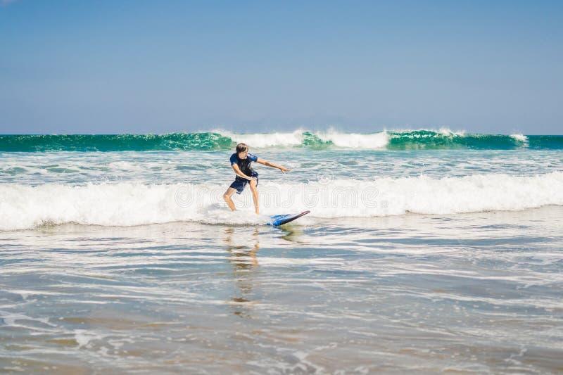 Молодой человек, серфер beginner учит заниматься серфингом на пене моря на b стоковые фотографии rf