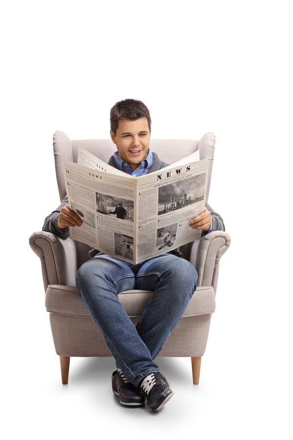 Молодой человек сидя в кресле и читая газету стоковое фото