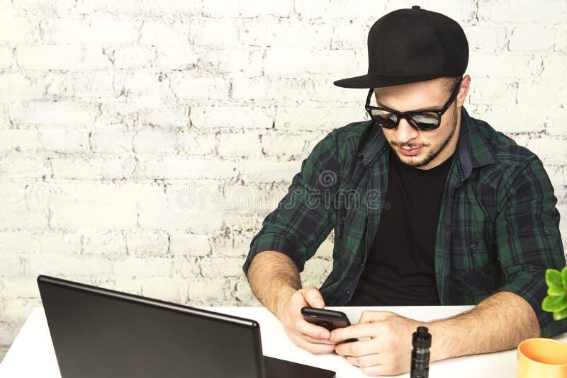 Молодой человек сидя в офисе с чашкой кофе и vaping стоковые изображения