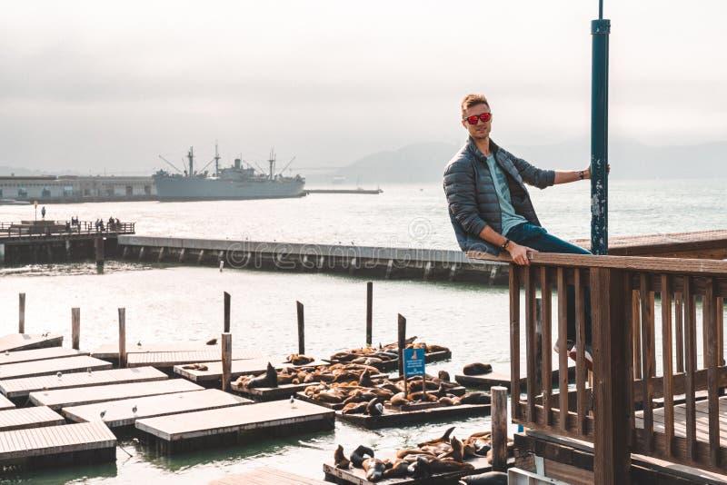 Молодой человек сидя в Сан-Франциско с изумительным городским взглядом около пристани 39 стоковое изображение