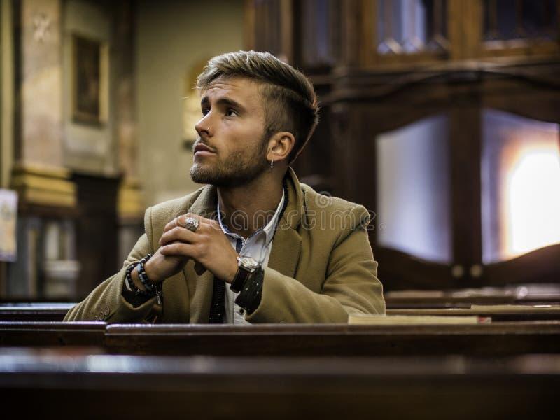 Молодой человек сидя в церков стоковые фотографии rf