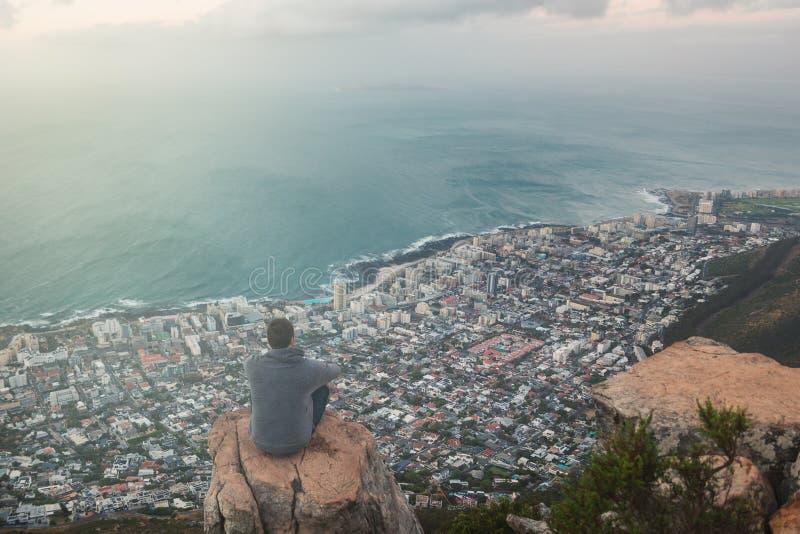 Молодой человек сидя на крае вверху гора льва главная в Кейптауне стоковые фото