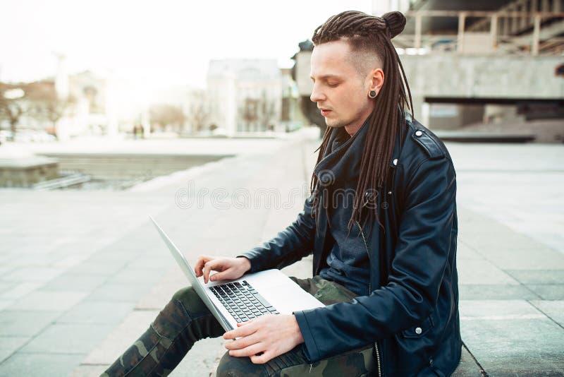Молодой человек сидя на лестницах используя ноутбук стоковое фото rf