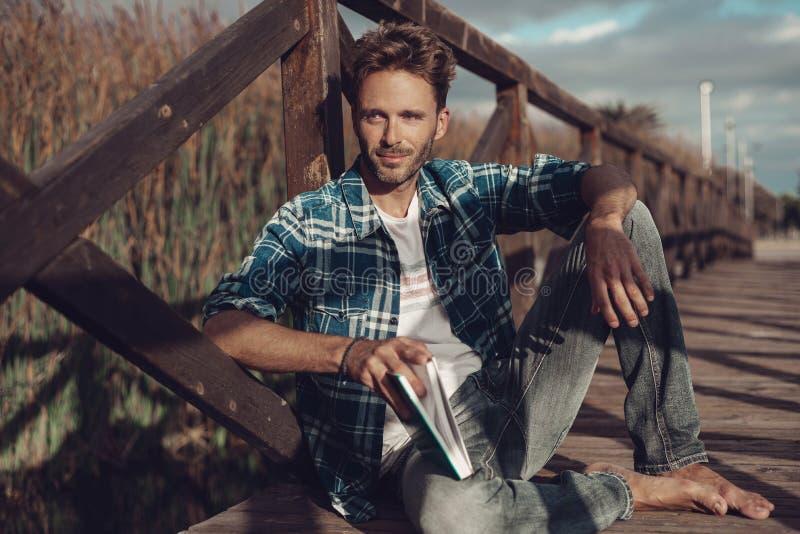 Молодой человек сидя на мосте стоковая фотография