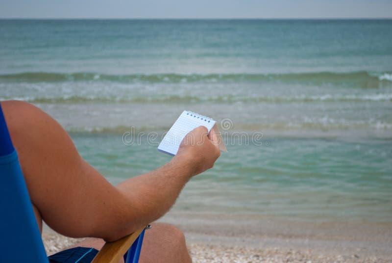 Молодой человек сидя на deckchair на береге, держа тетрадь для примечаний в клетке, отдыхая загорать стоковые фотографии rf