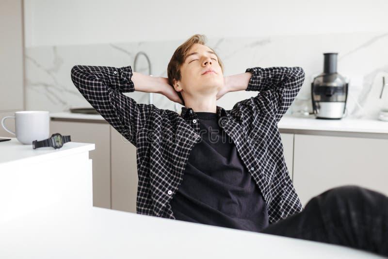 Молодой человек сидя с чашкой и наблюдать dreamily закрывать его глаза держа руки за головой в кухне стоковые изображения