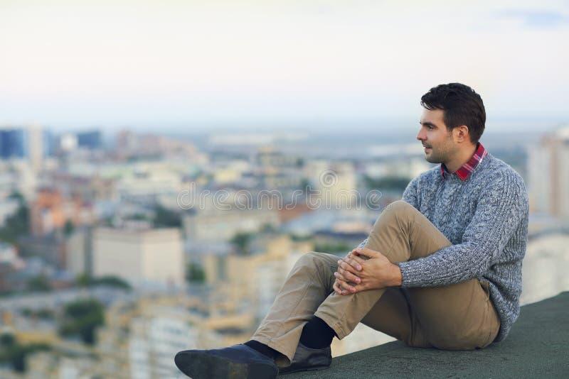 Молодой человек сидя outdoors на крыше стоковые фотографии rf