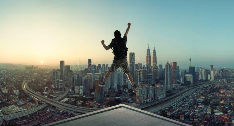 Молодой человек скача на крышу с большим взглядом восхода солнца городского пейзажа стоковые изображения