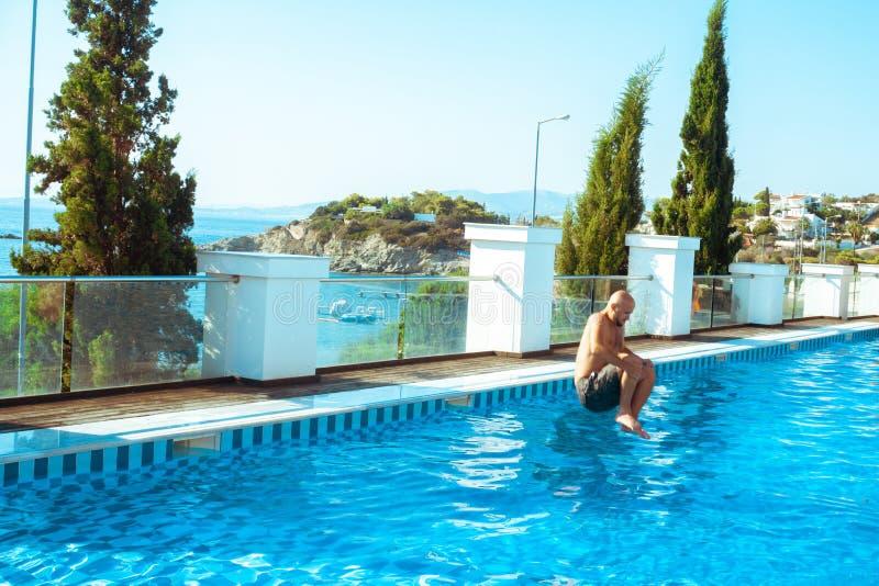 Молодой человек скачет в бассейн стоковые фото