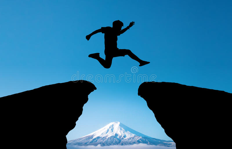 Молодой человек скачет над горой и до конца на зазор силуэта холма выравнивая красочное небо стоковые изображения rf
