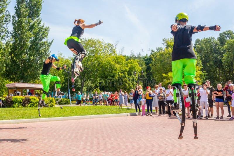 молодой человек скачет на прыгунов на обваловке Рекы Волга на день лет стоковое изображение