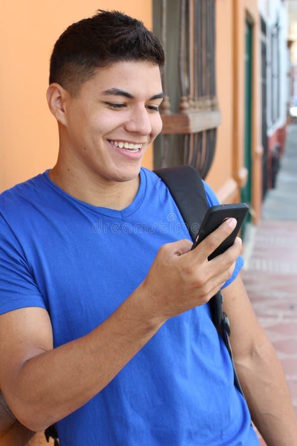 Молодой человек смеясь на мобильном телефоне стоковая фотография