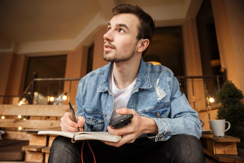 Молодой человек смотрит небо, он держит его тетрадь с ручкой, и смартфон Он сидит на террасе кафа стоковые фотографии rf