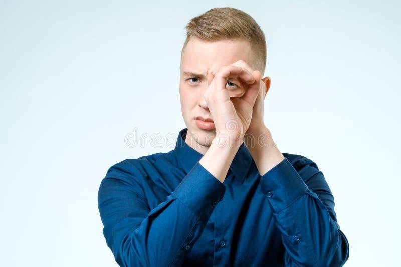 Молодой человек смотря далеко изолированный на белизне стоковое фото