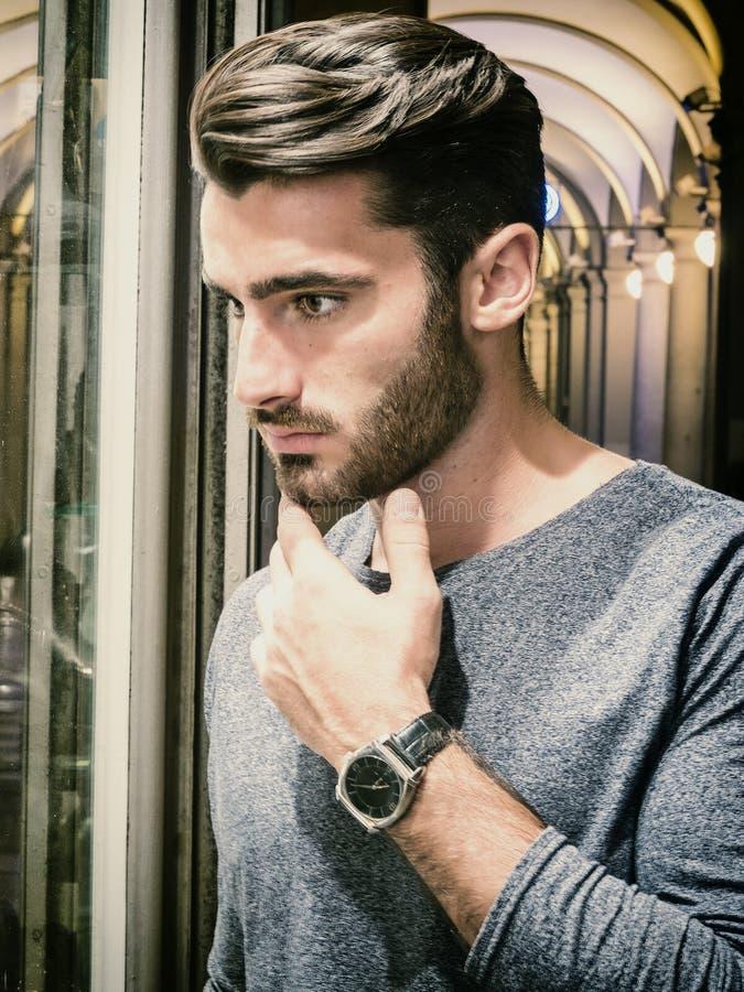 Молодой человек смотря детали моды в окне магазина стоковая фотография