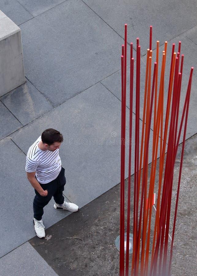 Молодой человек смотря дизайн искусства около моста в Денвер, Колорадо тысячелетия стоковое изображение