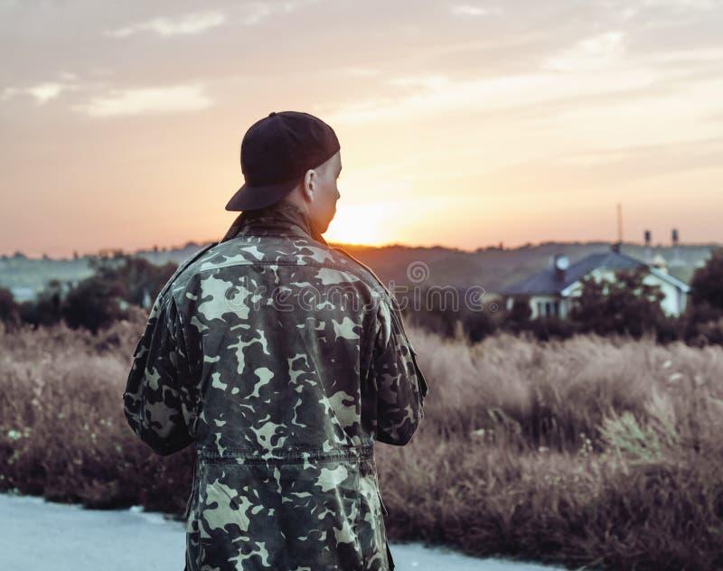 Молодой человек смотря заход солнца стоковое фото rf