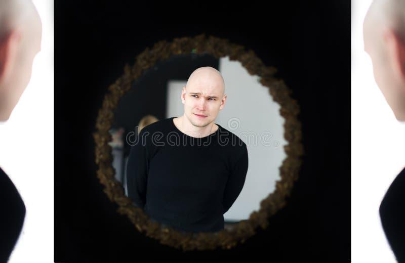 молодой человек смотря зеркало Поиск  сознавание стоковые фото