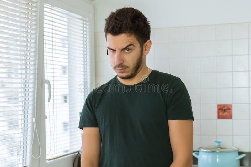 Молодой человек смотря камеру в сюрпризе стоковое изображение