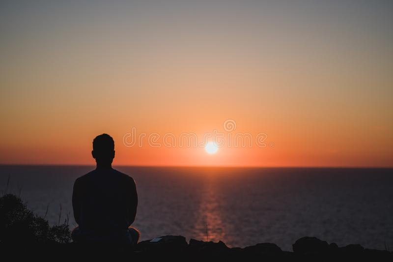 Молодой человек смотря к заходу солнца над морем Наслаждаться и расслабляющая концепция, полные незабываемых опытов для того чтоб стоковое изображение