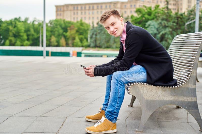 Молодой человек со смартфоном сидя на стенде улицы города, космосе экземпляра стоковая фотография rf
