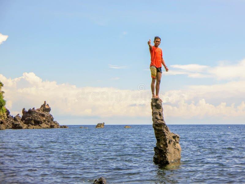 Молодой человек стоит на каменном столбце в море Скала выступая от моря Скалистое побережье балийского моря E стоковая фотография rf