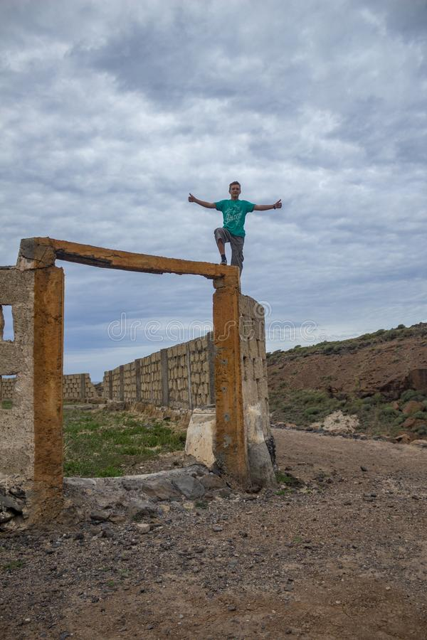 Молодой человек стоит на поперечине пустых ворот в получившуюся отказ плантацию банана Признак земледелия которое было нажато стоковое фото rf