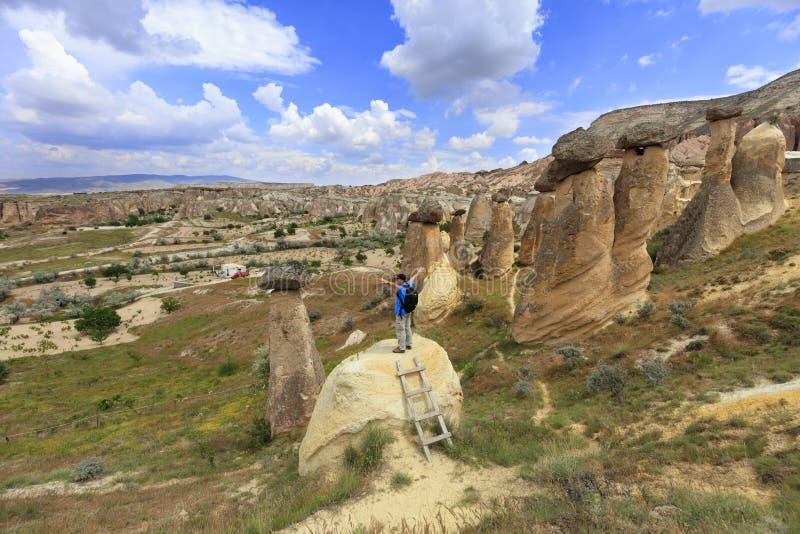 Молодой человек стоит на утесе и взглядах на раскрывая ландшафте и голубом небе в Cappadocia стоковое фото