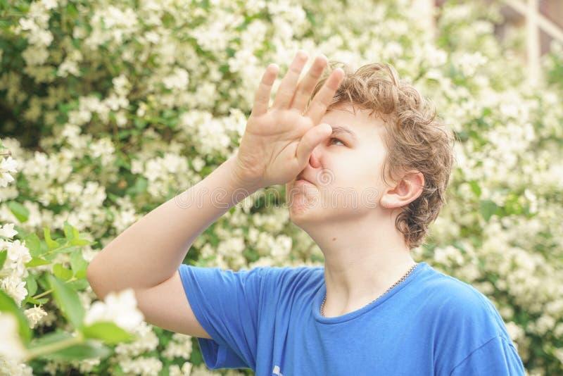 Молодой человек стоит среди цветков и наслаждается летом и цвести стоковые фотографии rf