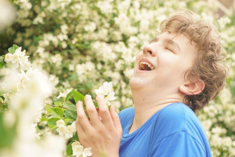 Молодой человек стоит среди цветков и наслаждается летом и цвести стоковая фотография rf
