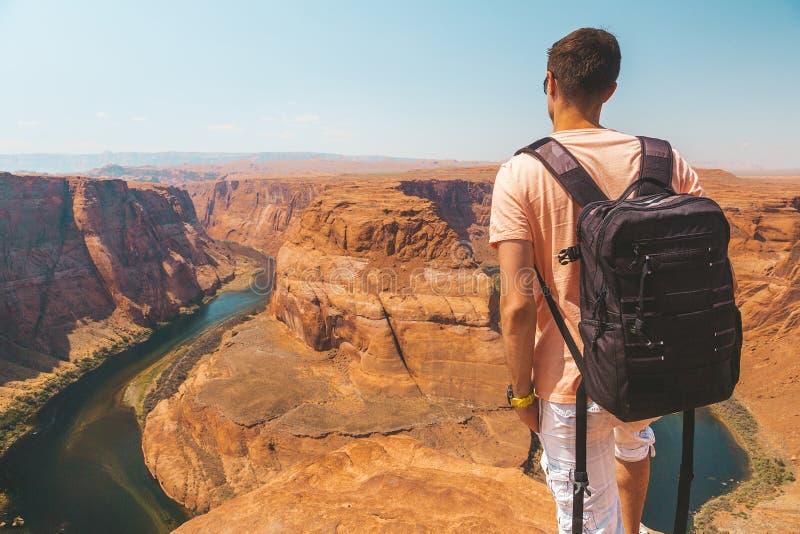 Молодой человек стоя на крае скалы загиба ботинка лошади стоковое изображение