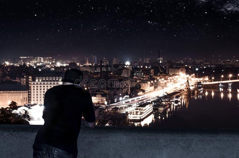 Молодой человек стоя на крыше высокого здания стоковое изображение
