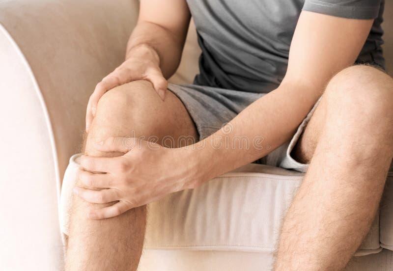 Молодой человек страдая от боли в ноге дома стоковые изображения