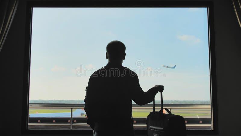 Молодой человек с багажем наблюдает, как самолет принимает из окна его гостиничного номера стоковое фото