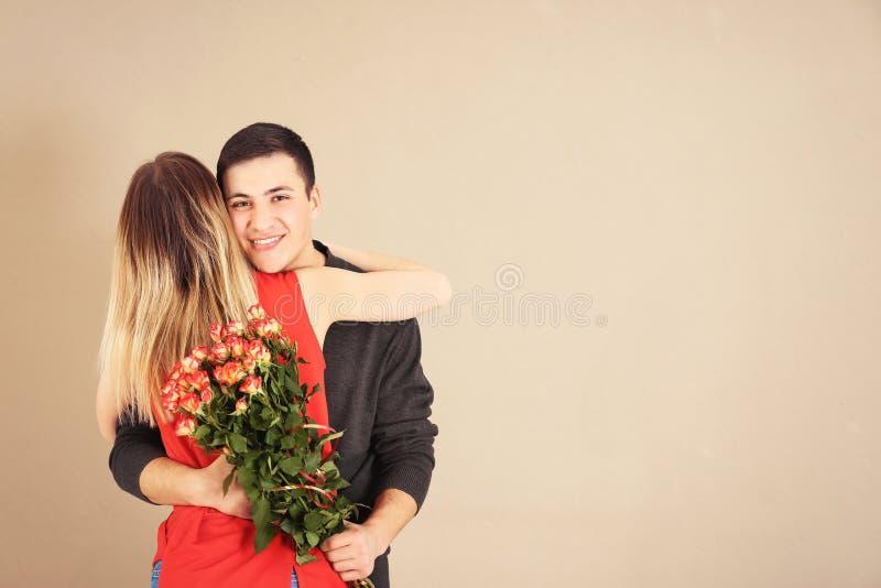 Молодой человек с букетом цветков обнимая его девушку на предпосылке цвета стоковая фотография rf